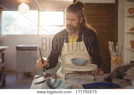 Attentive male potter painting on bowl in pottery workshop