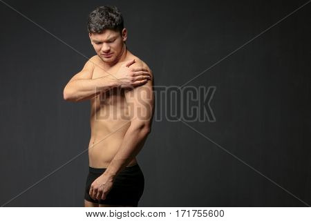 Young man suffering from pain in shoulder on dark background