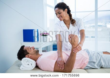 Physiotherapist giving hand massage to a patient in clinic