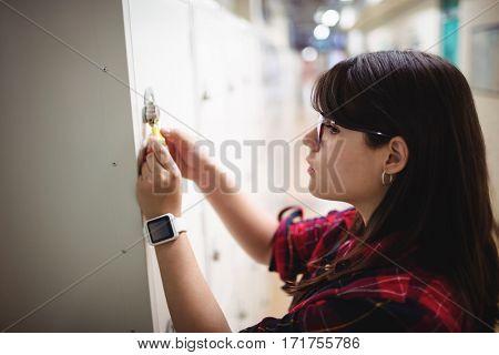 Female student locking her locker in college