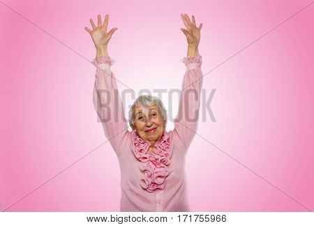 The portrait of a happy senior woman gesturing victory over pink background