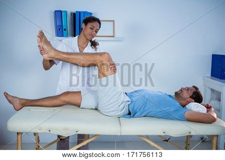 Physiotherapist giving leg massage to a patient in clinic