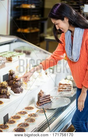 Happy woman selecting desserts from display in supermarket