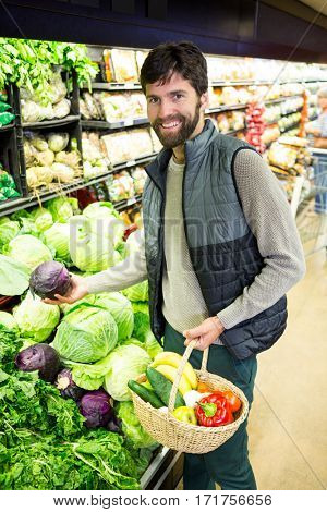 Man with wicker basket buying vegetables in organic shop at super market