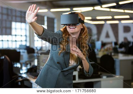 Cheerful woman gesturing while using virtual reality simulator in office