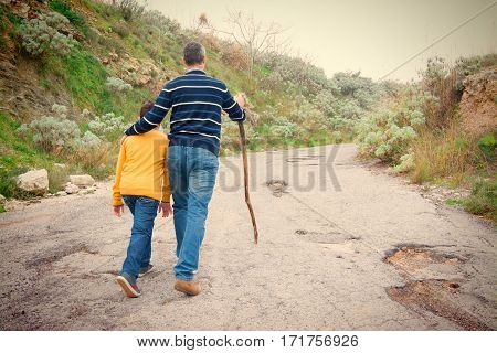 Father accompanies his son in an uphill climb. Teaching concept to life