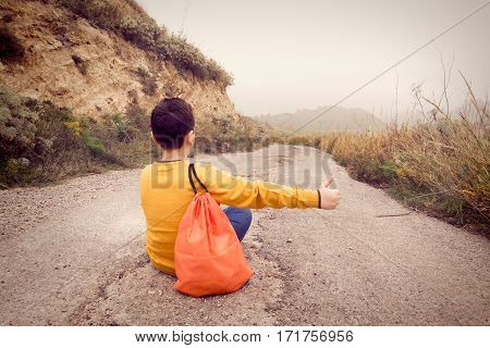 Teenager sitting on the street waiting for the passage of a car