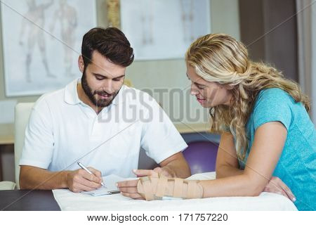 Physiotherapist writing report next to the patient in clinic