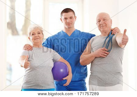 Physiotherapist with elderly patients in clinic