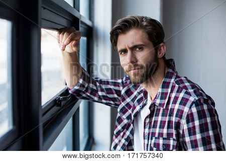 Portrait of young businessman standing by window in creative office