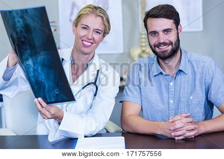 Portrait of physiotherapist showing x-ray to a patient in clinic