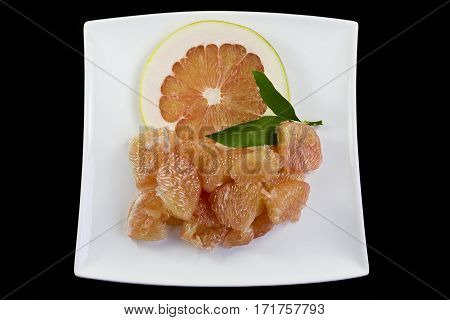 Pink flesh of a pomelo citrus maxima on black background