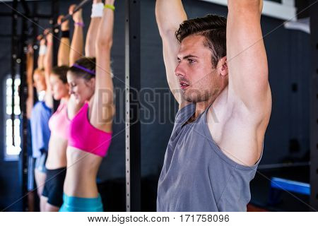 Man doing chin-ups while hanging in gym