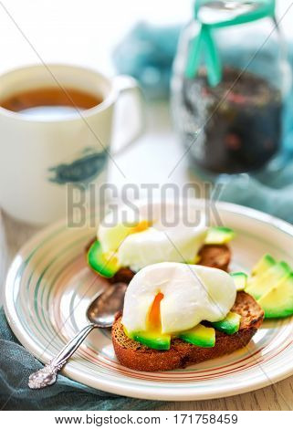 Sandwiches with avocado and poached eggs on plate. Cup of tea in the light background. Concept of home breakfast. Vertical image