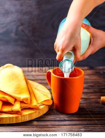 Children's hands pouring milk from a glass bottle. Pancakes on a wooden Board nearby. Wooden dark background. Concept of homemade Breakfast