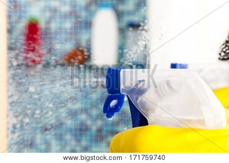 Person doing chores in bathroom at home cleaning mirror with spray detergent