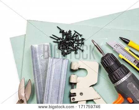 Plasterboard tools set with screws tape measure screwgun cutter marker pen metal studs and snips on white background