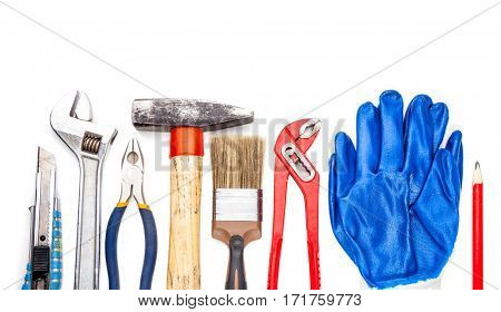 Work tool collection on white background with cutter adjustable spanner pliers hammer brush work gloves and a pencil