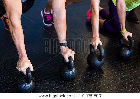 Low section of athletes exercising with kettlebells in gym