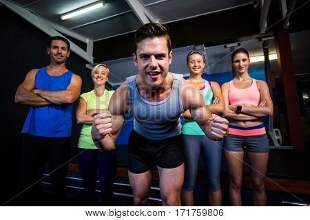 Portrait of cheerful handsome athlete clenching fist while in gym