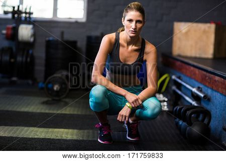 Portrait of young female athlete crouching in fitness studio