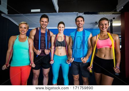 Portrait of happy male and female athletes with resistance band in fitness studio