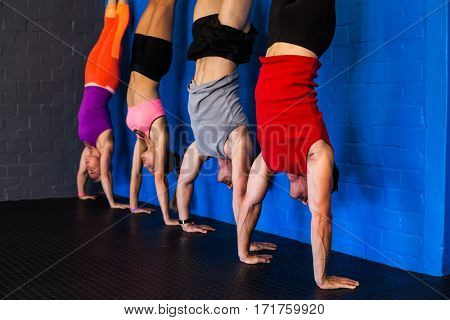 Male and female athletes practicing handstand against wall in fitness studio
