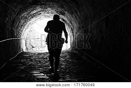 Man coming out of a dark tunnel. black and white.