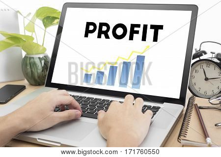 hand typing on keyboard and Profit homepage on the computer screen in workplace. business finance concept.