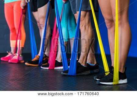 Low section of athletes exercising with resistance band in gym