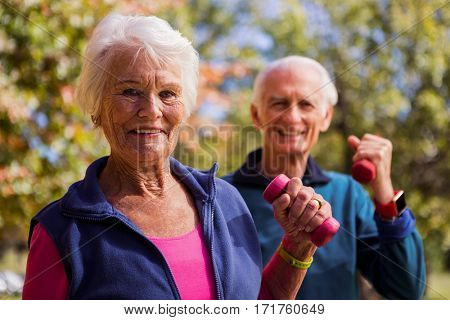 Elderly couple making fitness and lifting hand weight in the park