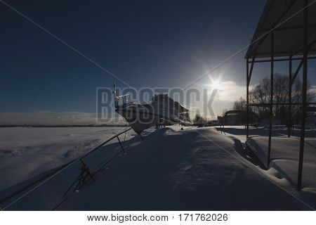 Frozen ship staying on river covered ice at winter sunny day, silhouette, wide angle