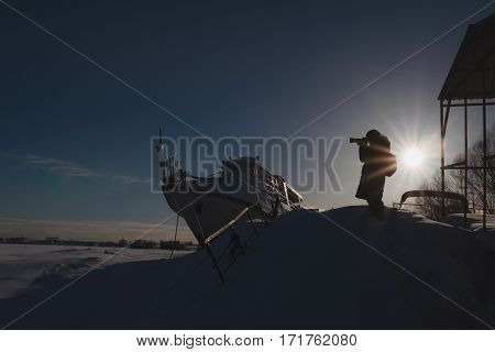 Photographer travels and takes pictures. Russian ice harbor near vessel at sunny day, silhouette