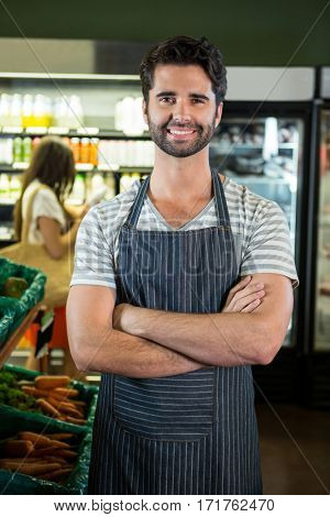 Portrait of smiling male staff standing with arms crossed in organic section of super market