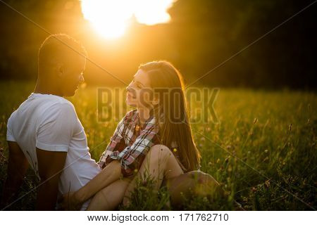 Young couple talking together on date - sitting in grassfield at summer sunset