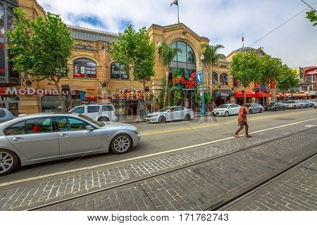 San Francisco, California, United States - August 14, 2016: Luxury car street parade on Jefferson road. New BMV car and a homeless crossing the street. Concept of opposite lifestyles in the road.