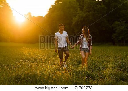 Young couple walking in grassfield and holding hands - summer evening with sunset
