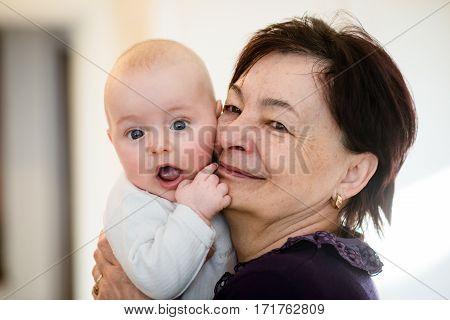 Grandmother is hugging with her baby grandson - indoors scene