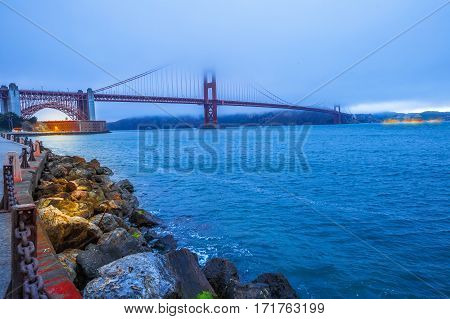 Golden Gate Bridge with fog from Fort Point at dusk, San Francisco Bay, California, United States. Symbol, icon and landmark of San Francisco. Urban cityscape panorama. Travel and holidays concept.