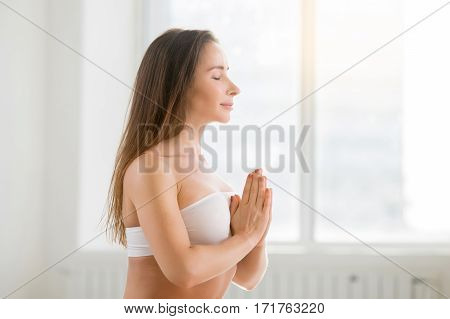 Young attractive yogi woman practicing yoga, making namaste gesture, her eyes closed, working out, wearing sportswear, sport bra, indoor, white color background, closeup side view portrait