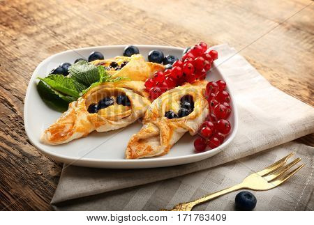 Tasty puff pastry with berries on plate