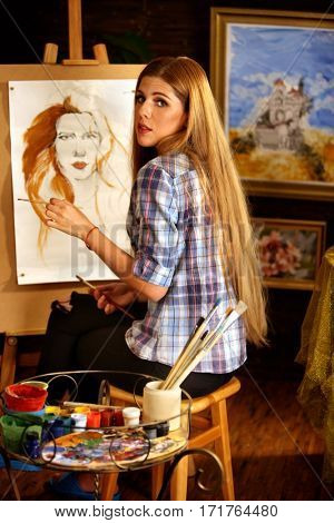 Artist painting on easel in studio. Girl paints portrait of woman with brush. Female painter seen from behind. Indoor home interior for handmade crafts. Drawing lesson in his own studio.