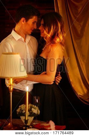 Couple dancing and kissing indoor. Romantic evening interior for loving couple. Happy people in love. Burn golden candle in foreground.