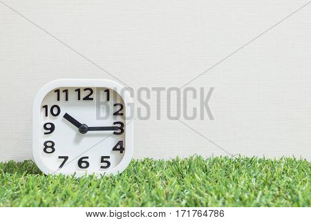 Closeup white clock for decorate show a quarter past ten or 10:15 a.m. on green artificial grass floor and cream wallpaper textured background with copy space