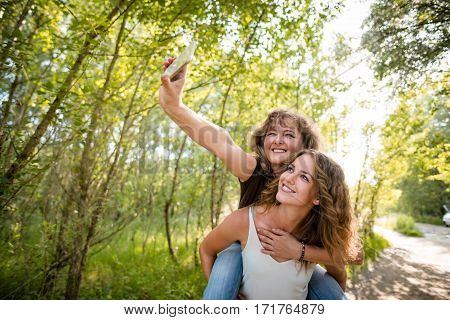 Mother taking a selfie with daughter while enjoying piggyback ride