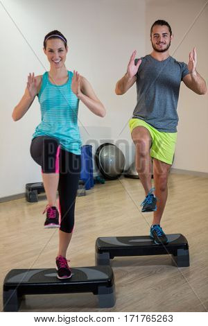 Smiling man and woman doing step aerobic exercise on stepper in fitness studio