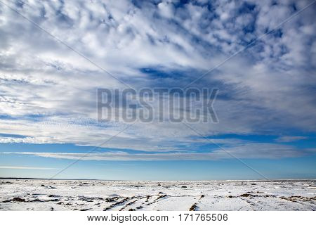 Wide sky panorama idyllic of the North sea frozen in the ice. Beautiful nature water frozen in the winter. Landscape snowy expanse to the horizon with a wonderful sky and clouds.