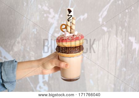 Hand holding milkshake, donuts and other sweets in glass on color background