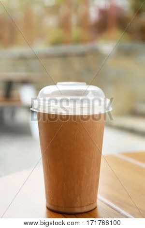 Plastic cup of delicious cool drink on wooden table