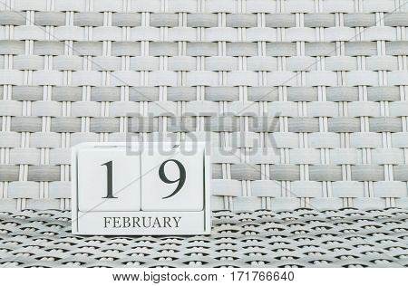 Closeup surface white wooden calendar with black 19 february word on blurred weave wood chair textured background with copy space in selective focus at the calendar